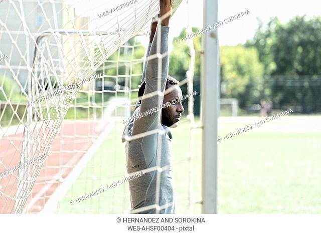 Sportsman standing on soccer field at goalpost