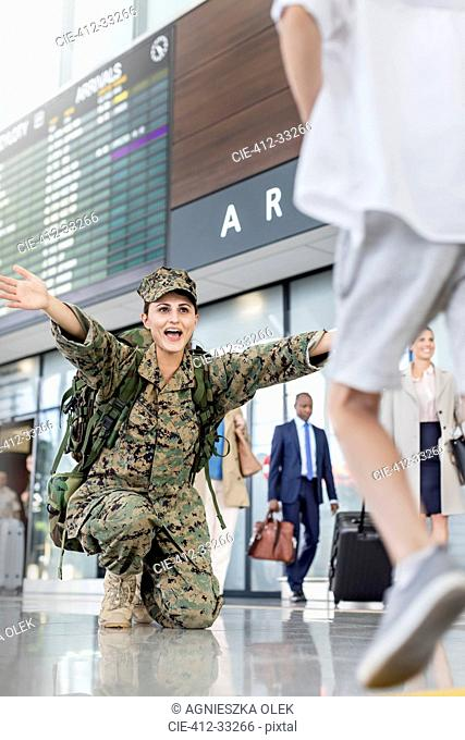 Son running greeting mother soldier at airport
