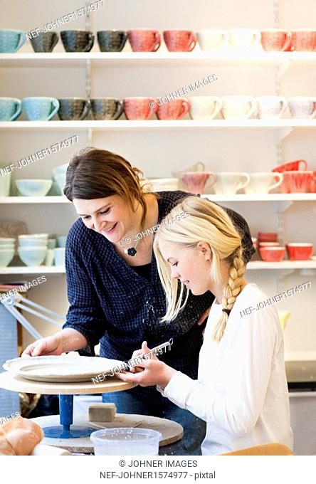 Smiling woman and girl making pottery plate