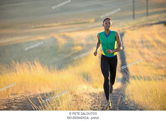 Young woman running on dirt track, Bainbridge Island, Washington State, USA
