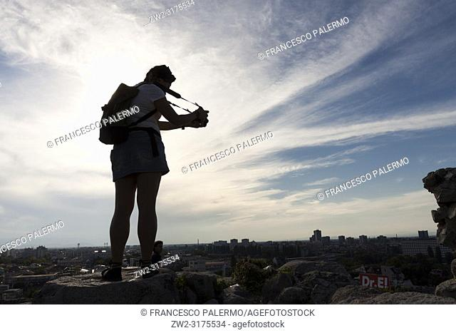 Young woman photographs the panorama at sunset. Plovdiv, Bulgaria