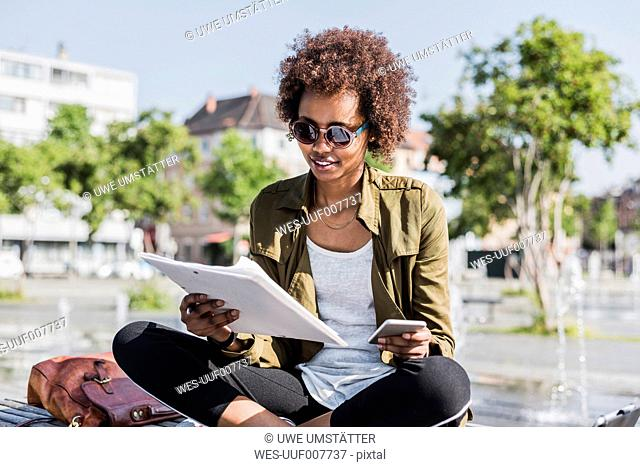 Portrait of young woman sitting on a bench reading notes