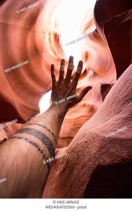 USA, Arizona, tourist in Lower Antelope Canyon, raised arm, tattoo