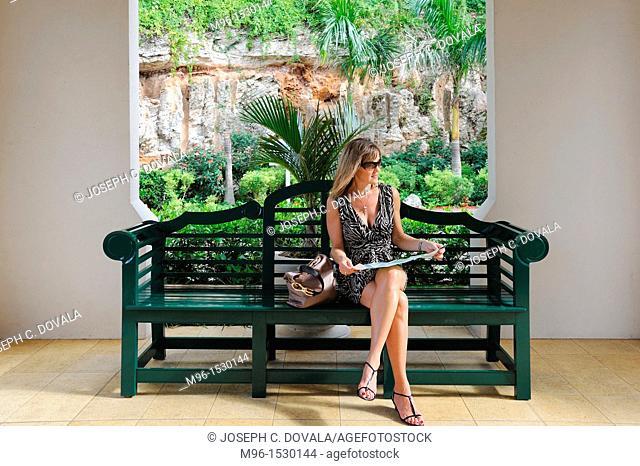 Woman sitting on bench looking at map, Bermuda Island, Atlantic