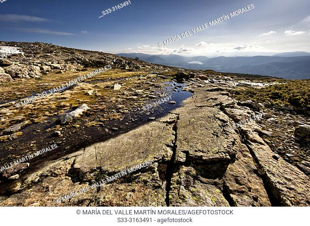 Thaw at National Park of Penialara Lagoons and Universls Hills and Pinilla reservoir on the background. Sierra de Guadarrama. Madrid. Spain
