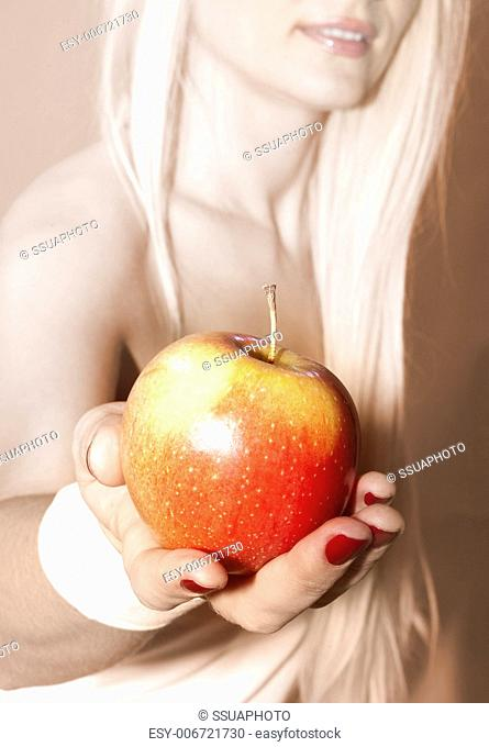 close up of female hand that suggests to take apple