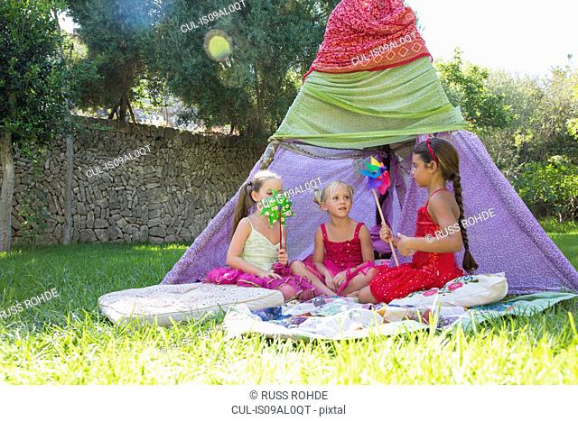 Three girls playing with pin wheels in front of teepee