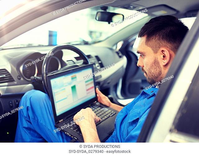 mechanic man with laptop making car diagnostic