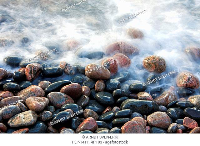 Close up of colourful pebbles covered by wave on shingle beach at rising tide