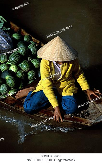 High angle view of a woman sitting in a boat with fruit, Vietnam