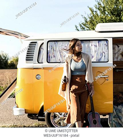 Pretty woman on a road trip with her camper, drinking beer, holding guitar