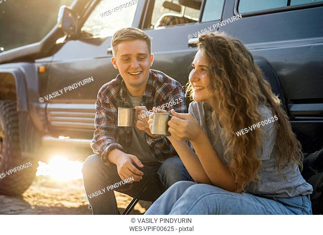 Young couple sitting by car, taking a break, drinking tea