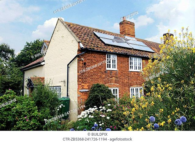 English cottage with solar panels on the roof