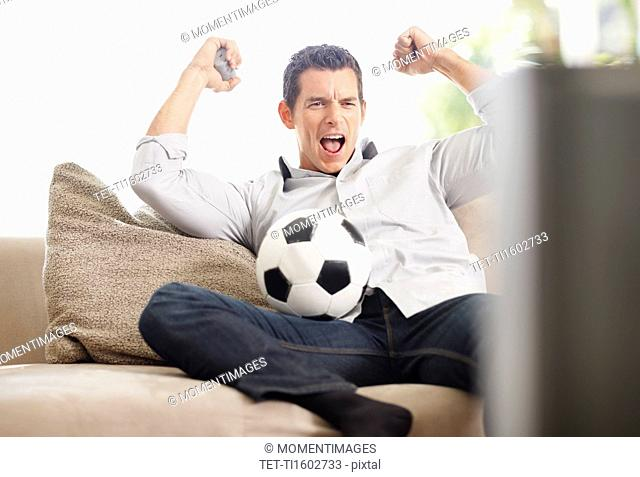 Mid adult man watching football match on television