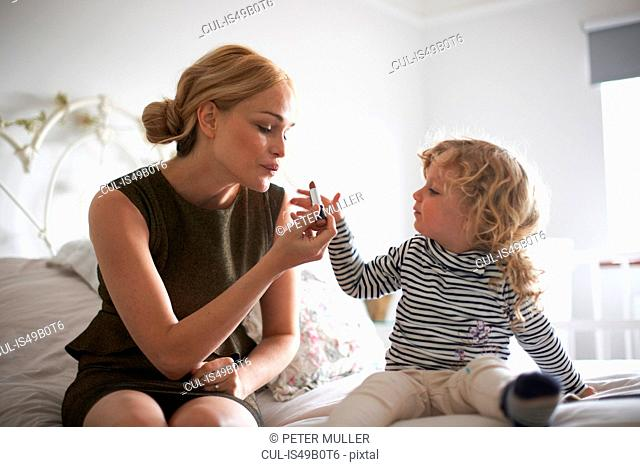 Daughter helping mother put on lipstick