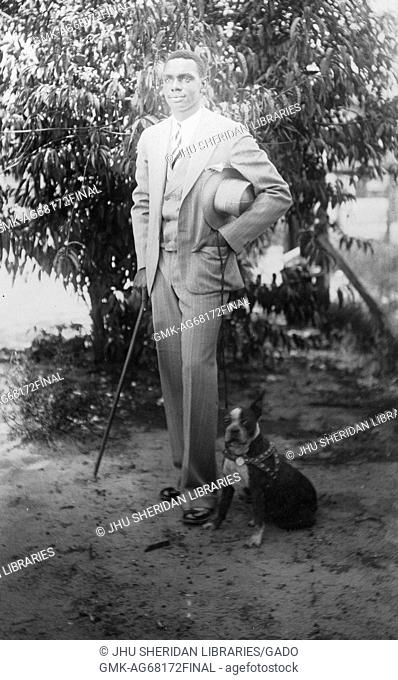 Full length standing portrait of young African American man, wearing light suit with vest, light shirt, striped tie, holding hat, cane and dog leash