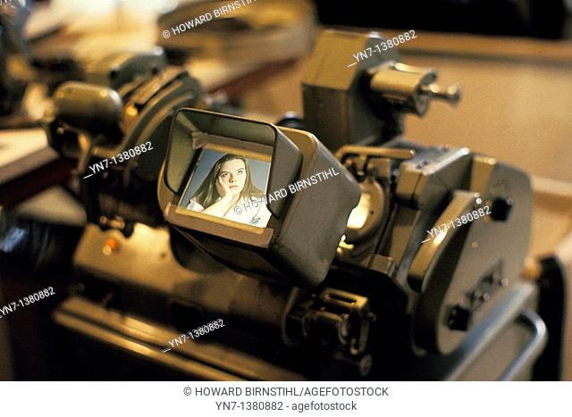 close up of a 35 mm movie film editor viewer with an image of a young girl on the screen