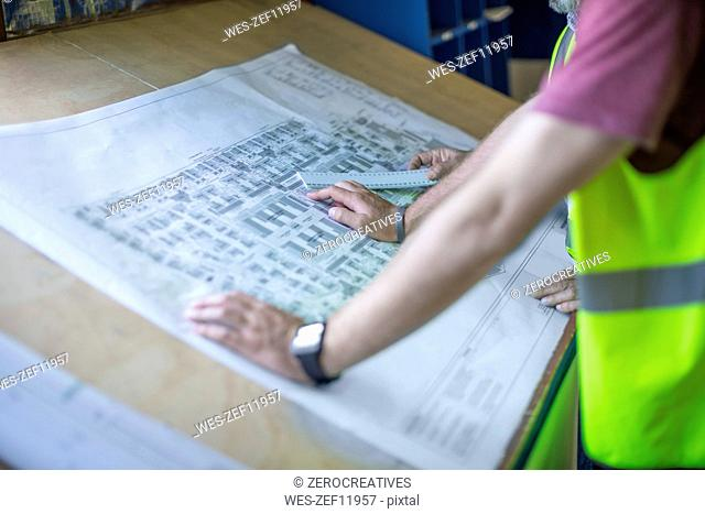 Engineers looking at blueprints in site office