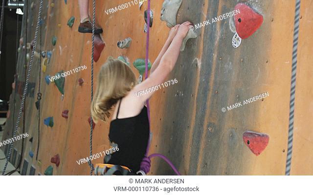 little girl on an indoor climbing wall