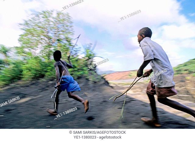 Two young boys running, Sulphur Bay Village, Tanna Island, Vanuatu
