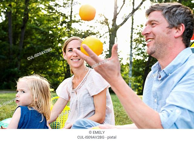 Mature man juggling oranges at family picnic in park