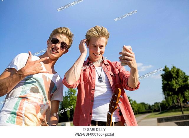 Germany, Young man is making rock' roll sigh, while friend is checking his looks
