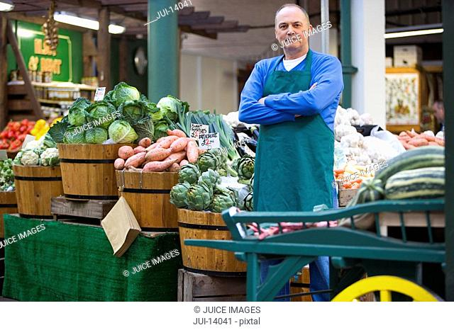 Green grocer with arms crossed by produce, portrait