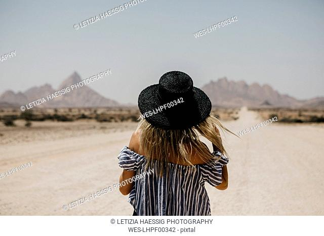 Namibia, woman wearing a hat on the road to Spitzkoppe