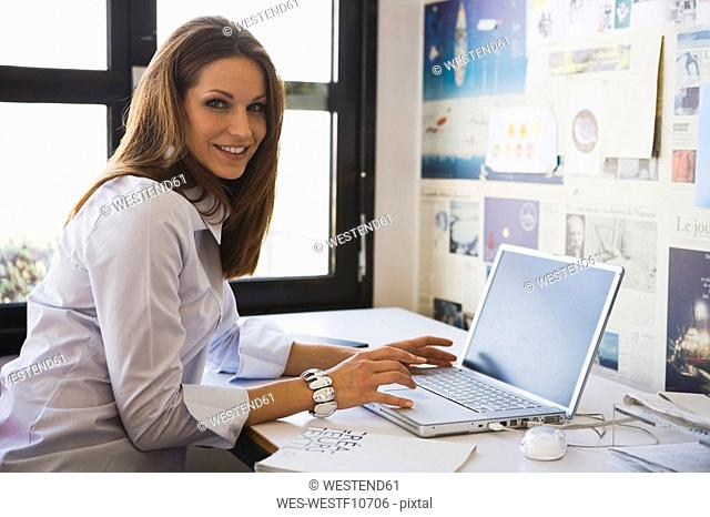 Young woman in office using laptop, portrait