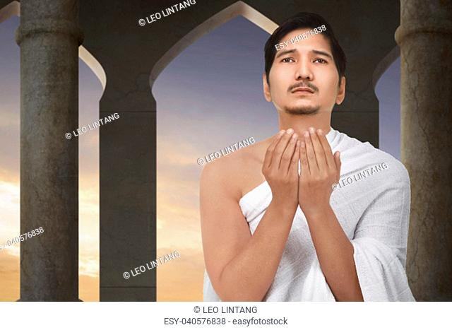 Attractive asian muslim man praying to god on the mosque