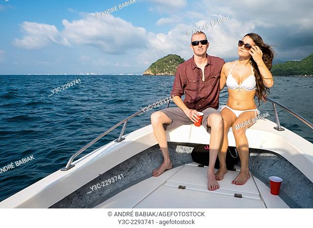 Young woman and man in swimsuits enjoying a private boat tour to Los Arcos National Marine Park, Pacific ocean, Banderas Bay, Mexico