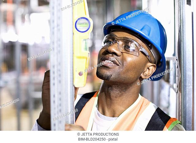 African American worker checking metal on site