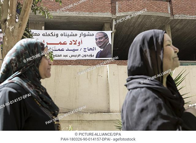 dpatop - Egyptian women walk in front of a banner of Egypt's President Abdel Fattah al-Sisi outside a polling station on the first day of the 2018 Egyptian...