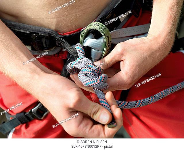 Close up of rock climber tying knot