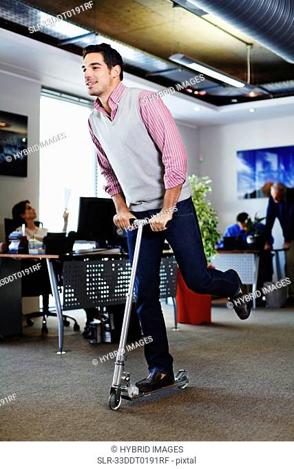 Businessman riding scooter in office