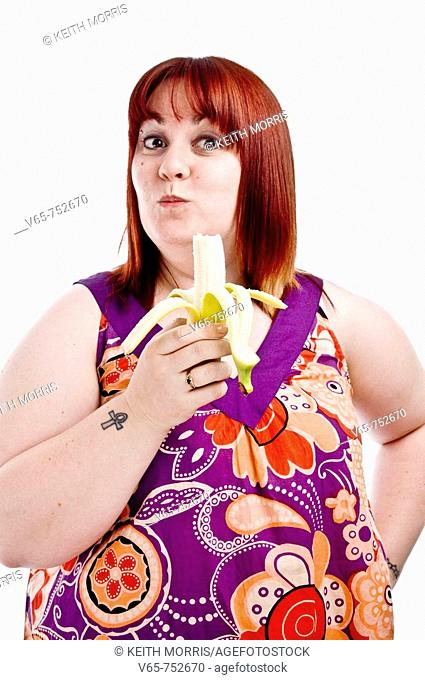 overweight fat young woman wearing bright coloured dress eating a banana