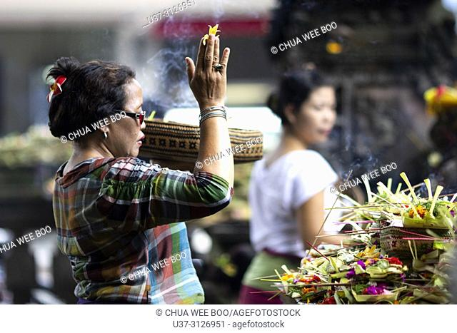 Balinese woman worshipping with flowers in Ubud, Bali