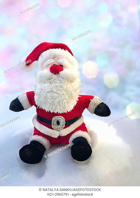 Textile Santa Claus sitting on a snow bank, behind a blurred background with bokeh