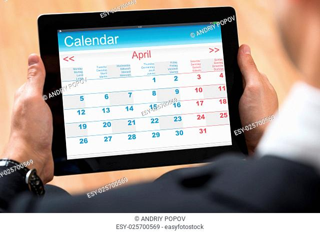 Close-up Of Businessperson Looking At Calendar On Digital Tablet