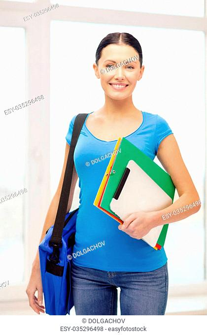 education, technology and school concept - smiling female student with folders, tablet pc and bag at school