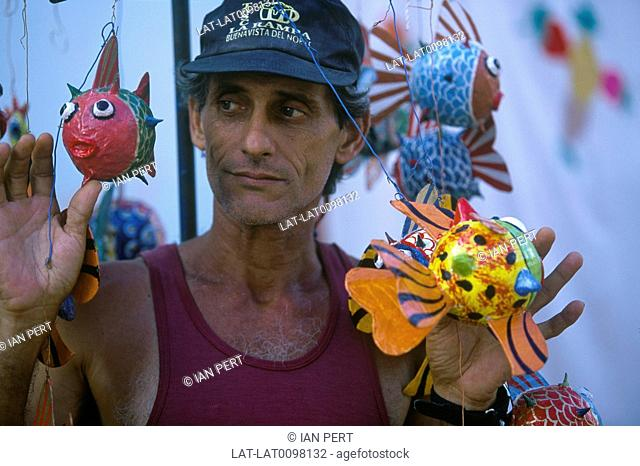 Man demonstrating papier mache models,fish with bright coloured bodies