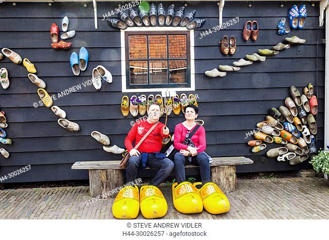 Europe, Netherlands, Zaandam, Zaanse Schans, Tourist Couple Posing with Giant Clogs