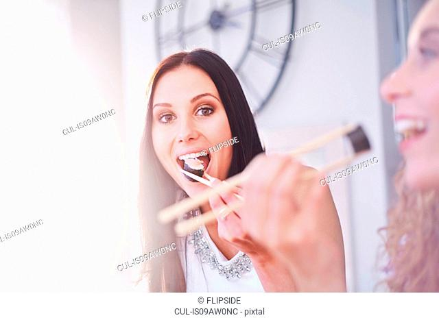 Two female friends eating sushi with chopsticks in kitchen