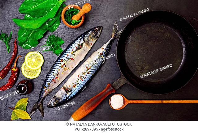 Two mackerels in spices and an iron cast-iron frying pan, top view