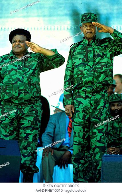 ANC leader Nelson Mandela and senior member Joe Modise stand at attention and salute an MK guard of honour during a parade in Soweto