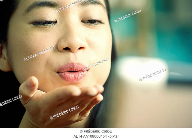 Young woman blowing kiss at camera while video conferencing