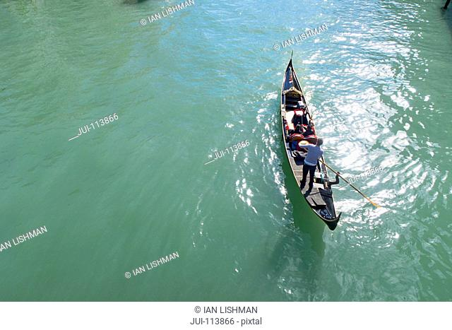 High angle view of gondolier paddling tourists in gondola in sunny canal in Venice, Italy