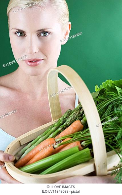 A young woman holding a basket full of vegetables