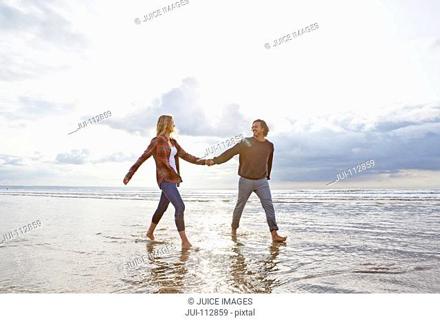 Couple walking and holding hands in ocean surf