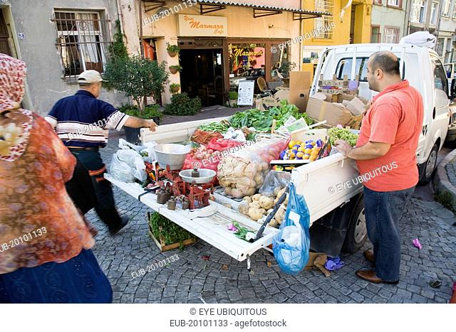 Sultanahmet. Fresh fruit and vegetable produce arrives by truck for local shoppers. Set of scales on tail gate with sacks of potatoes and boxes of oranges in...
